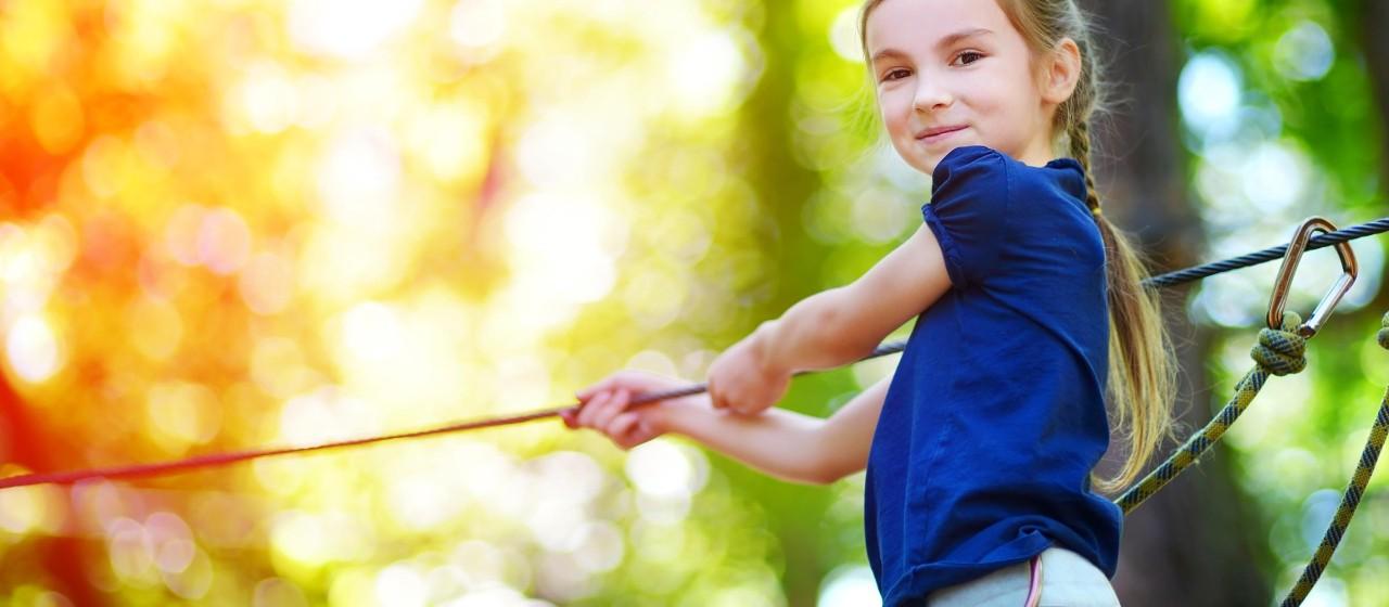 Mädchen gesichert mit Seil übt Klettern (Symbolbild)